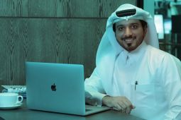 A man using a laptop while smiling.