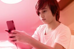 A young boy wearing a white t-shirt and looking at his smartphone.