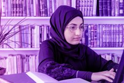 A young lady wearing a hijab and typing on her laptop.
