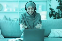 A woman wearing a hijab having a video call on her laptop.