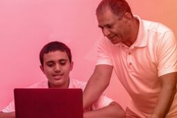 A father helping his son to do something on a laptop.