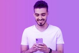 A youth using his smartphone while smiling.