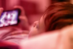 A child lying on a sofa and watching a video on a smartphone.
