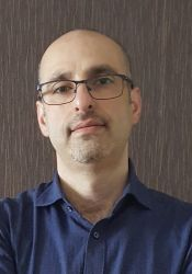 Raian Ali wearing a dark blue shirt and eyeglasses. The background is a brown wall.